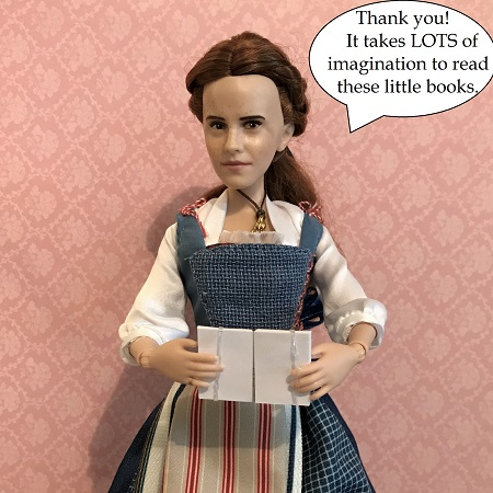 Image of Belle doll holding a blank book