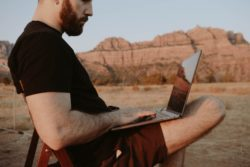 thoughtful man with laptop in countryside