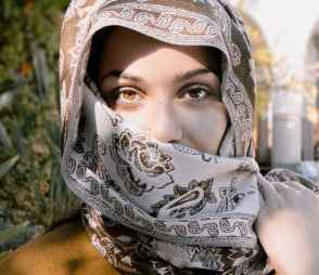 close up photo of a woman wearing brown and beige headscarf
