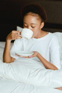 woman in white crew neck t shirt holding white ceramic mug