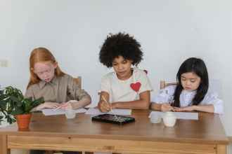 multiethnic cute little girls painting on papers sitting at desk in studio