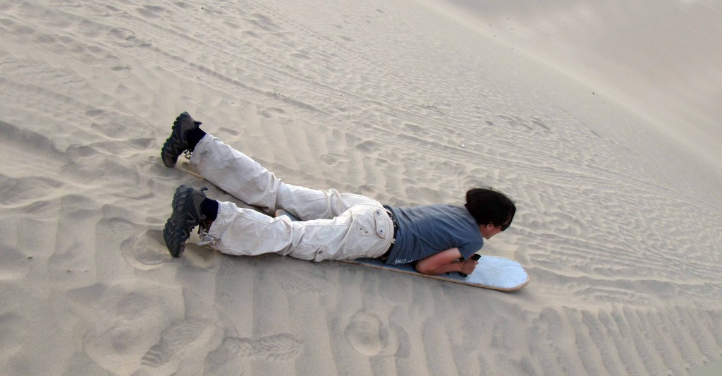 Practicando sandboard en las dunas. Practicing sandboarding in the dunes. Huacachina, Ica Photo credit, placeOK