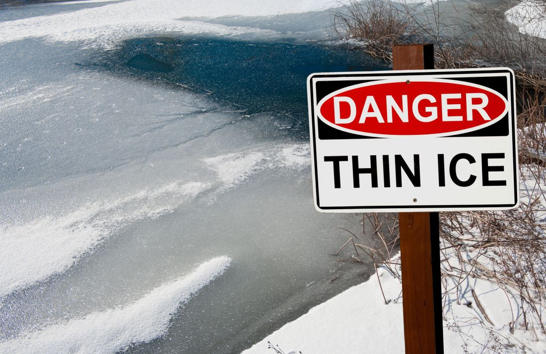 thin ice warning sign: a sign warns of danger as ice thaws on a pond in southern wisconsin.