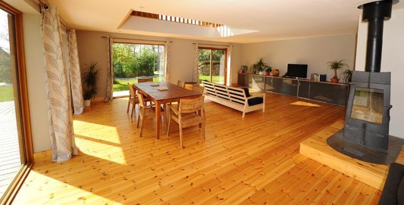 Intérieur maison bois avec cheminée et baies vitrées