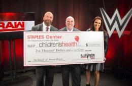 El Staples Center dona 10,000$ en nombre de Roman Reigns, Triple H y Stephanie McMahon reciben el cheque.
