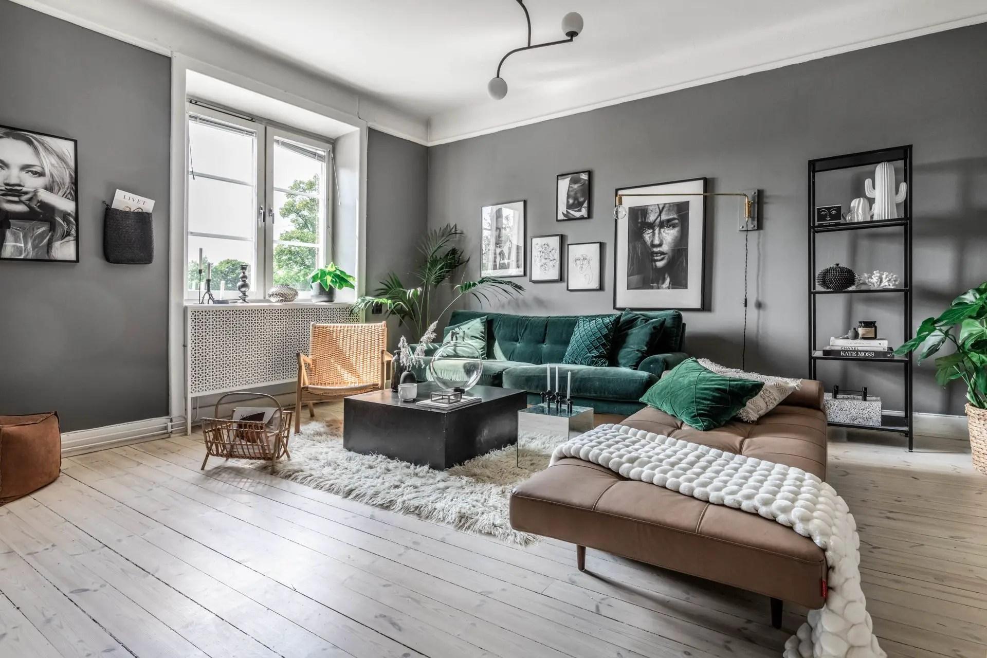 Un canapé en velours vert et des murs gris