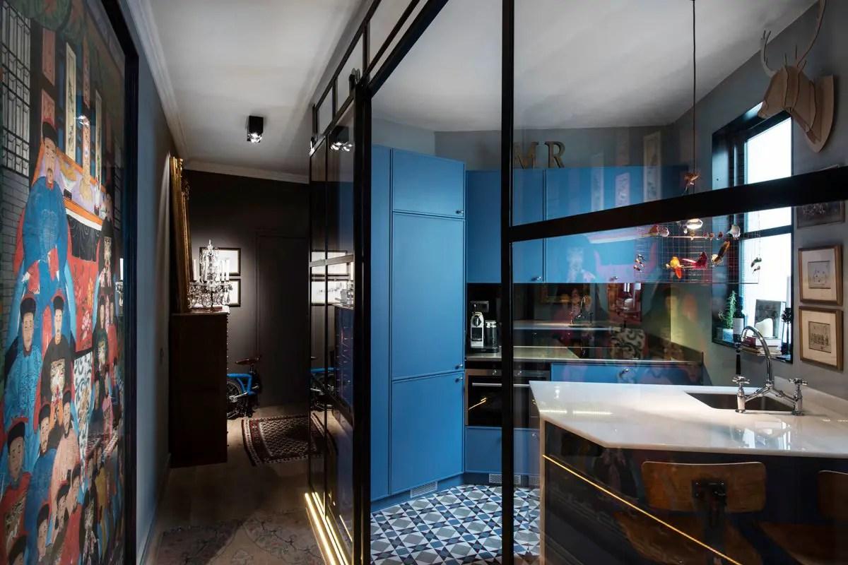 Une cuisine vitrée et bleue dans un appartement avec terrasse