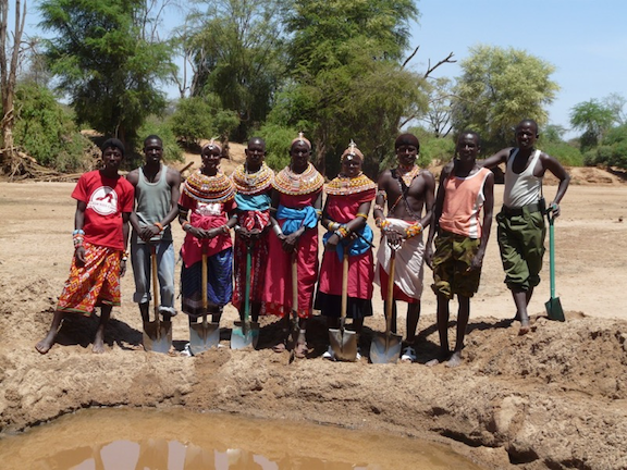 Ewaso Lions staff and community members dig side-by-side to create water holes for people and wildlife in Samburu.  (Image: Ewaso)