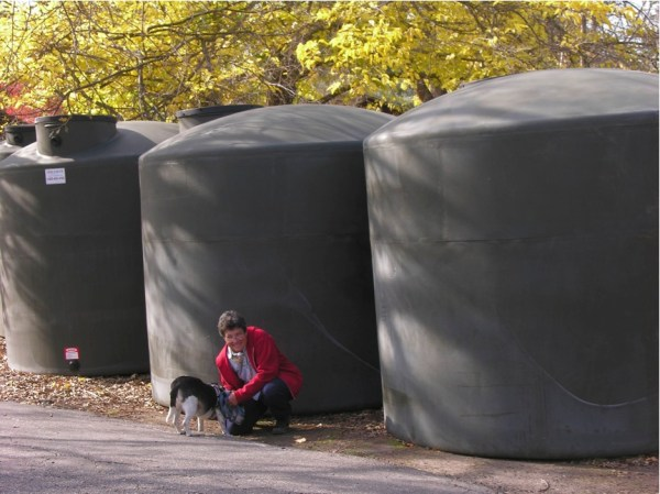The author against the 3,000 gallon rain tanks she uses to maintain her food plants and a natural pond intended to restore amphibian populations. (Photo Credit: Judy Adler)