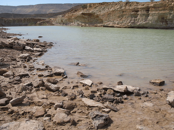 Water in Makhtesh Ramon after a flood in the Ramon river. Negev, Israel. (Photo Credit: Yuvalr / WikiMedia Commons)
