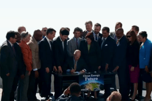 Gov. Jerry Brown (D-CA) signing SB 350. (Photo Credit: The California League of Conservation Voters)