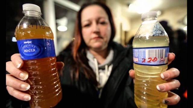 Flint resident LeeAnne Walters shows water samples from her home. (Photo via @DisabledScholar)