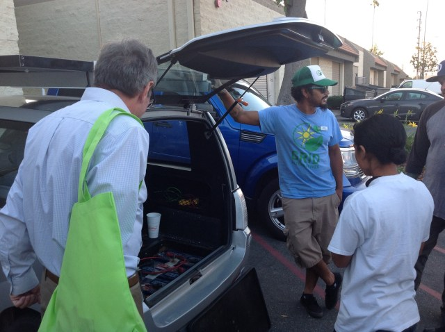 Ernesto Rochester shows of his electric vehicle equipped with modified solar panels. (Photo: Cameron Phillips)