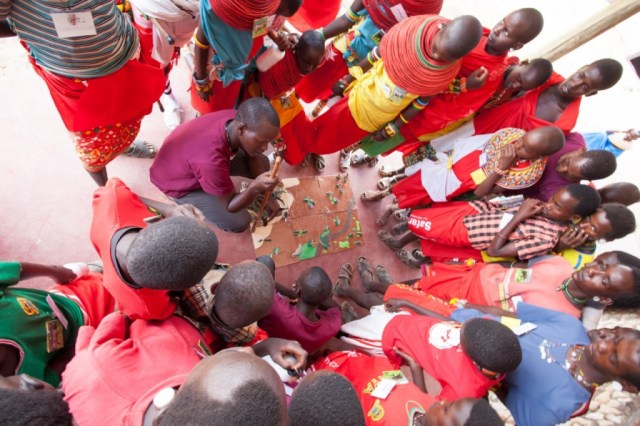 Kalastar teaches the children about safe herding practices using a model of a boma. (Photo Credit: Tony Allport)