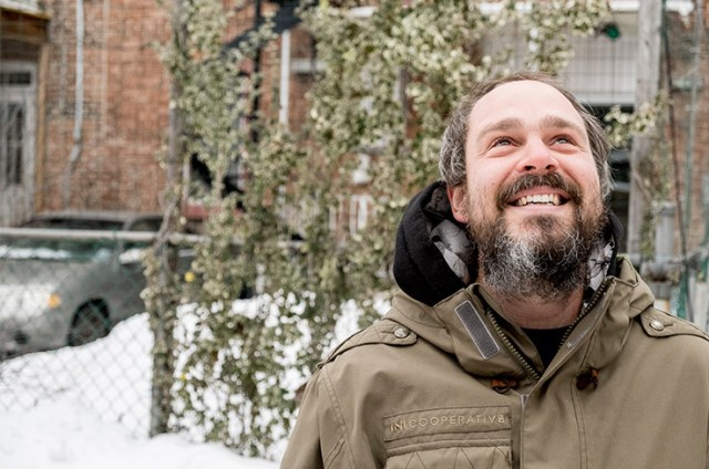 """Nicholas Legault, in the green alley between Chabot and de Bordeaux Streets. """"There are a lot of birds singing here, even in winter,"""" he says, marveling at a tree alive with a chorus of birdsong. (© Adrienne Surprenant)"""