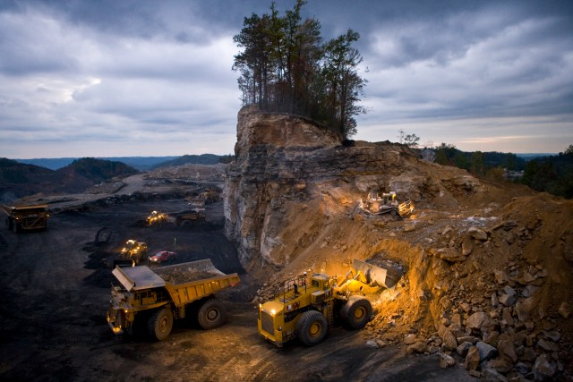 "Mountaintop removal coal mine at night. Mining operations work around the clock at amazing speed; this lonely stand of trees disappeared in barely a day. The small bulldozer on the upper level pushes loose material down to the loader, which scoops it up into the next earth mover in line which will dump it into a nearby ""valley fill,"" burying the stream there."
