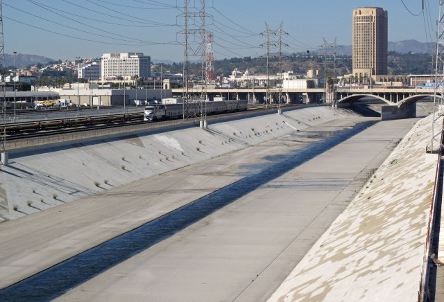 The Los Angeles River channel. Looking north from the Fourth Street Bridge — toward the Los Angeles County Metropolitan Transportation Authority headquarters building (tower). (Photo Credit: Downtowngal / WikiMedia Commons)