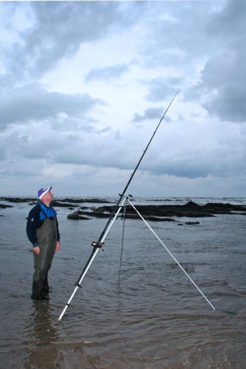 an angler on a rocky sore watches his rod tip