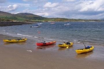 four brightly coloured kayaks on the beach