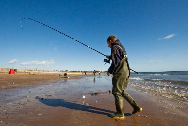 angler with a tiny flounder on Elliot beach