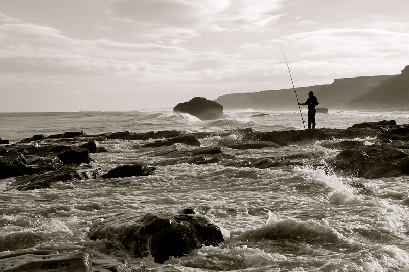 a lone angler on the rocks amid the waves