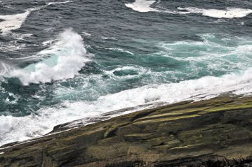 a rocky Orkney shore mark with swirling seas