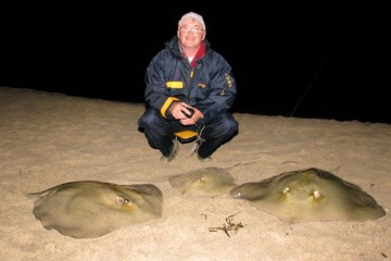 an angler on a Sardinian beach with three stingrays