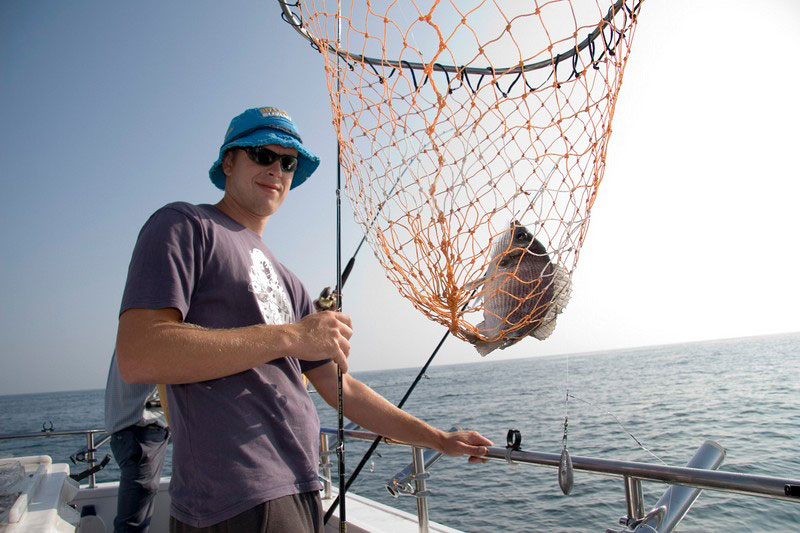 angler with black bream in net