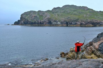an angler casting from the rocks in Cliffs Bay