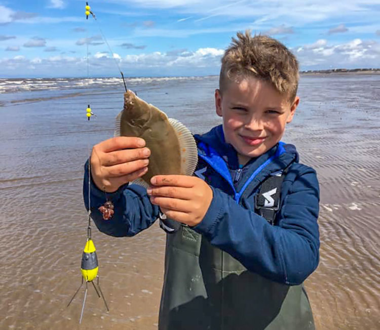 8 year old Archie Baxter with a plaice he caught at low water