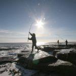 angler casting from an exposed rocky shoreline