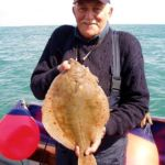 an angler displays a boat caught plaice