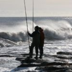 anglers on an exposed rocky shoreline with waves breaking