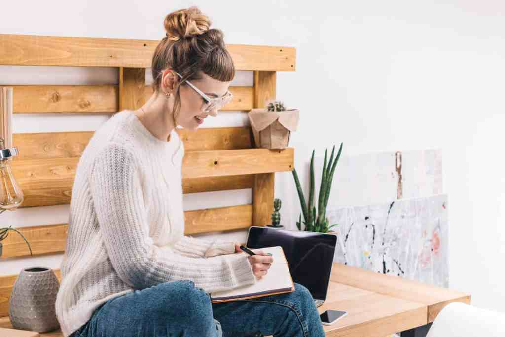 Girl sitting on bench writing out her plans to have the best year ever