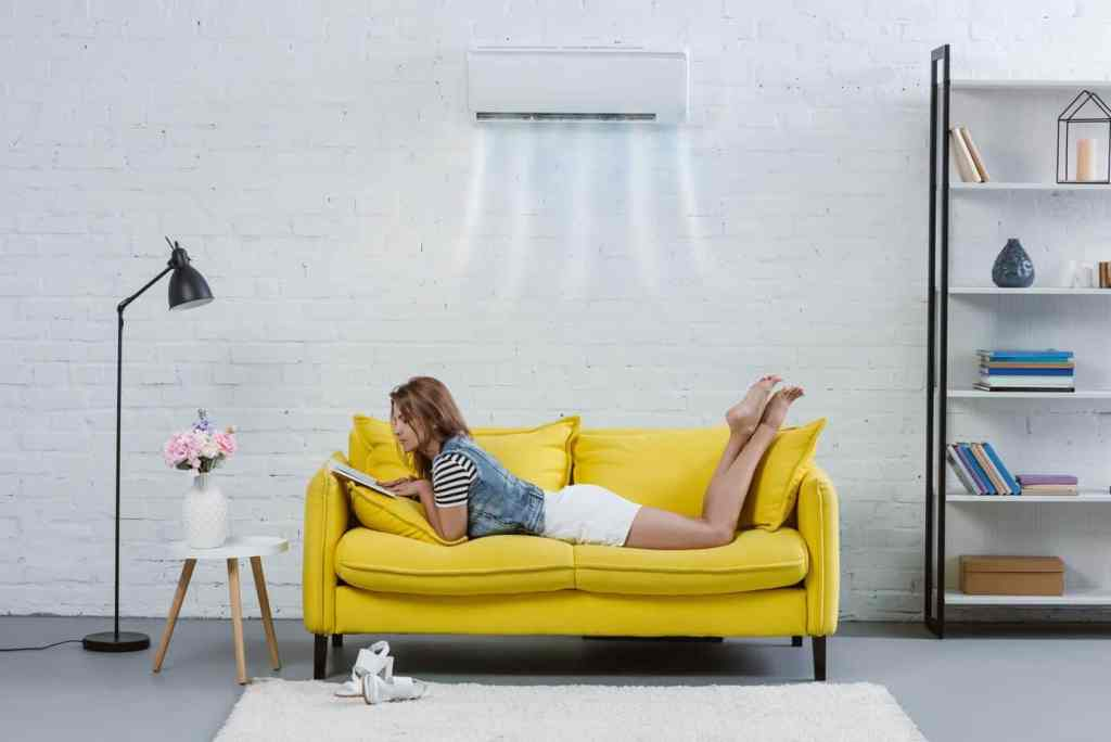 Woman reading on yellow couch as part of morning routine.