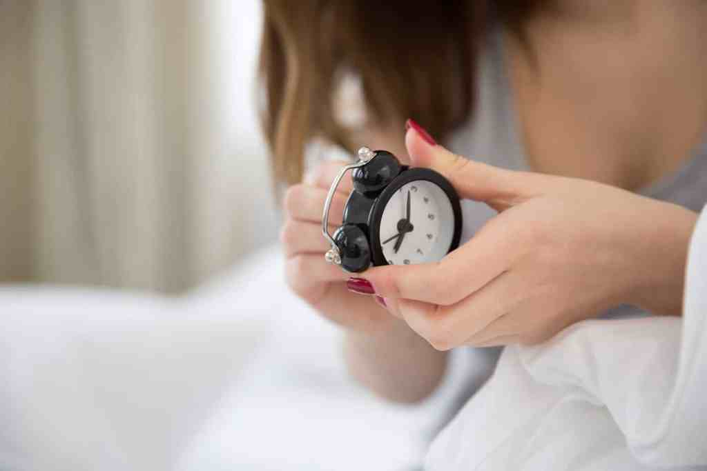 Setting alarm clock to get ready for tomorrow's morning routine.