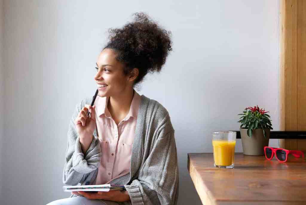Woman sitting at breakfast table thinking of ideas to plan her best year ever