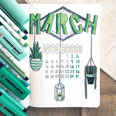 Bullet journal cover page for March with hanging plant doodles.