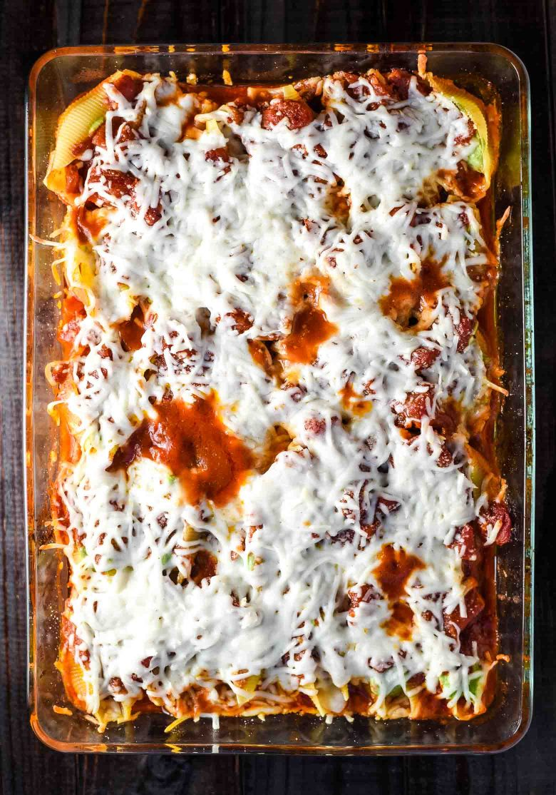 Vegan stuffed shells in a cooking pan with melted cheese on top.