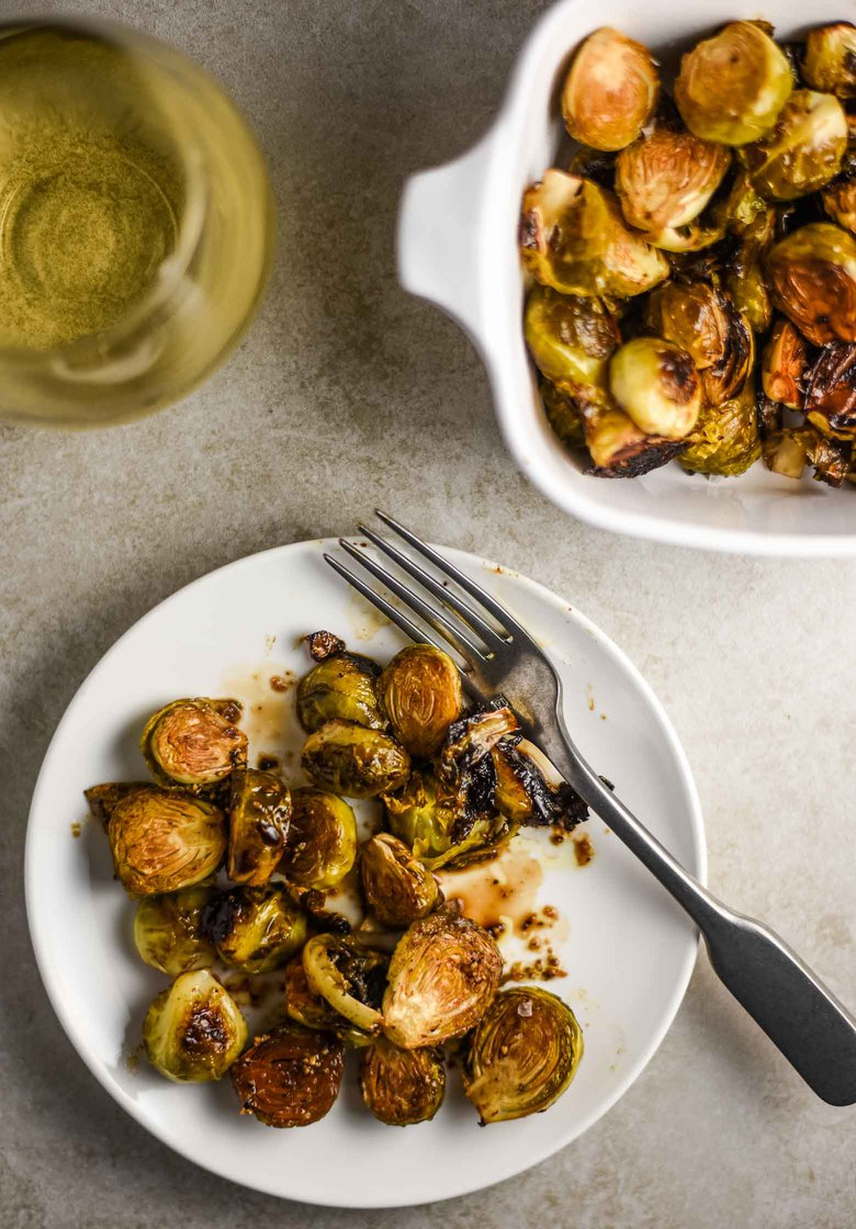 Balsamic roasted brussel sprouts on a white plate with a glass of white wine.