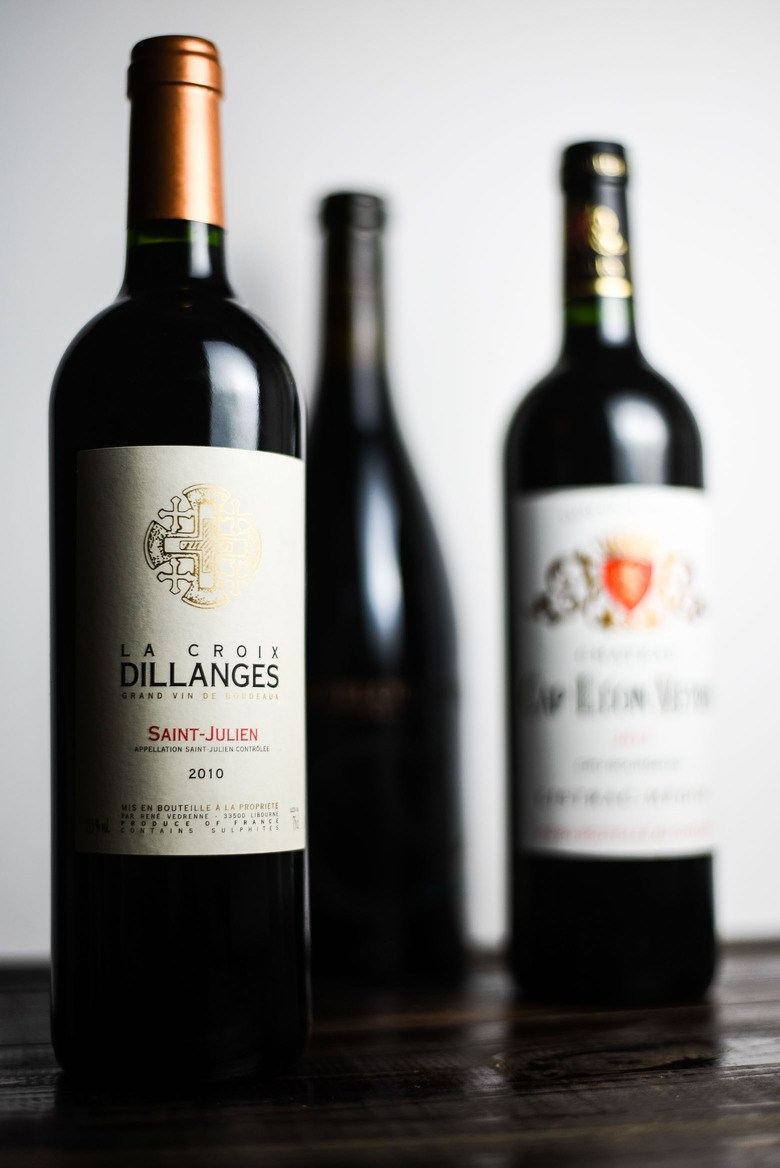 Holiday wine pairing guide with three bottles of red wine on a dark wood table