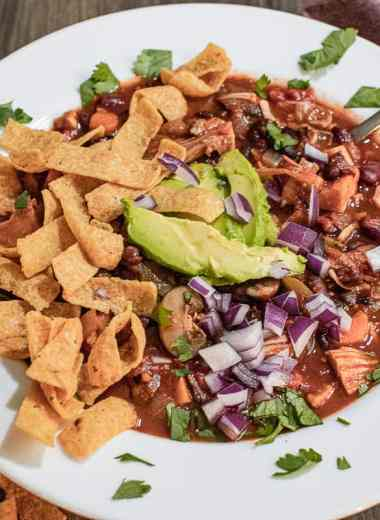Jackfruit chili in a white bowl topped with Frito chips, avacado, red onion and cilantro