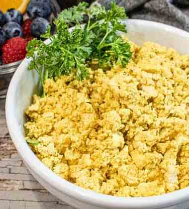 Scrambled tofu eggs in a white bowl with a sprig of parsely.