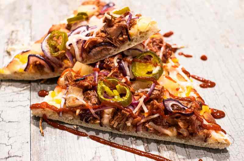 BBQ Jackfruit pizza slices on a cutting board.