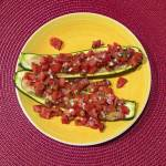 Zucchini halves stuffed with tomatoes on a yellow plate.