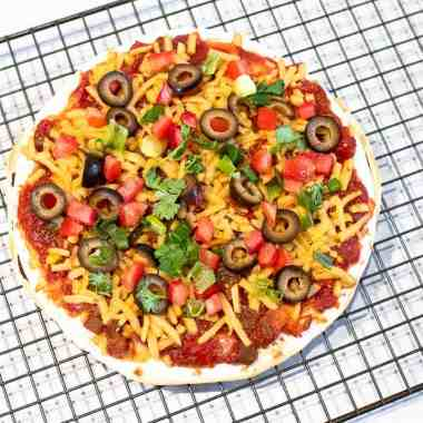Mexican pizza centered on a cooling rack
