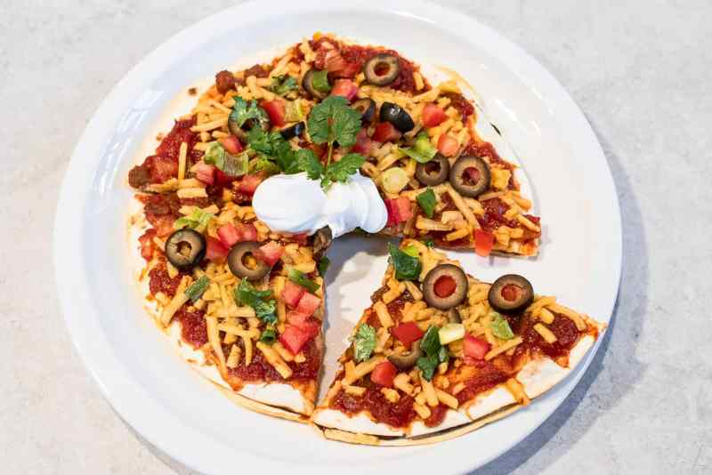 Mexican pizza with a dollop of sour cream