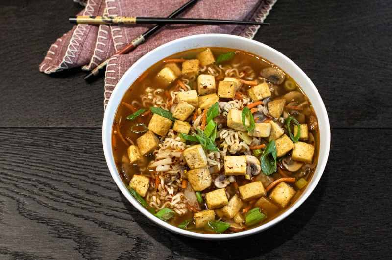 Hot and sour ramen soup with crispy tofu in a white bowl next to a napkin and chopsticks