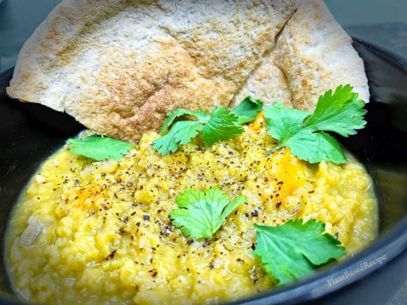 Vegan dahl served with bread, rice, vegetables