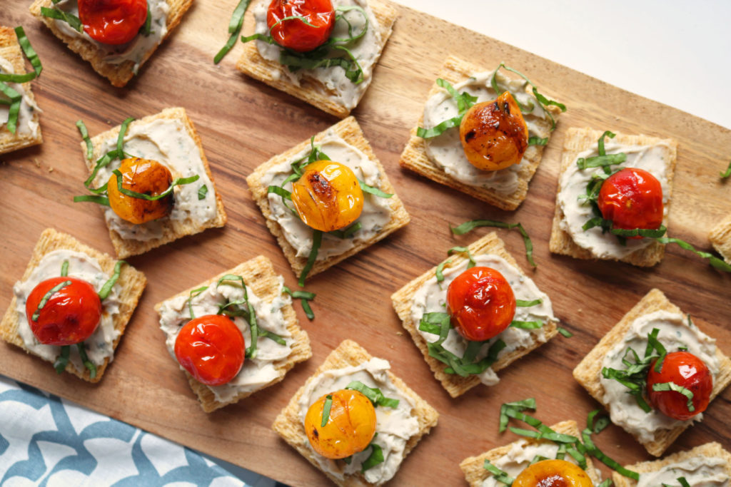 mini vegan toasts covered in tomatoes and vegan cashew cheese